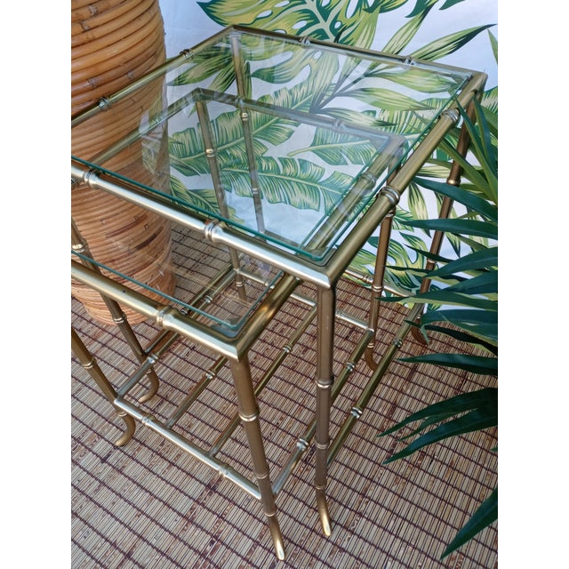 A set of 4 gold metal, faux bamboo nesting tables. The set features 2 tables per set which sit inside of each other. The...