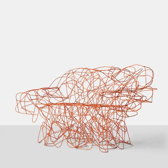 A sofa that is formed by the Campana Brothers from an irregular weave of stainless steel wire and painted with a coral...