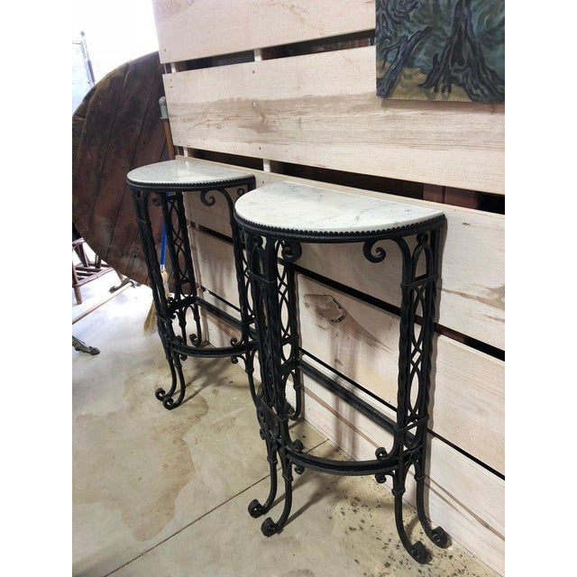 Antique French demilune iron tables with Carrara marble tops. Made in the late 19th century.