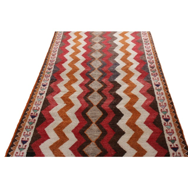 Made with hand-knotted wool originating circa 1910-1920, this antique Persian runner celebrates a classic Gabbeh rug...