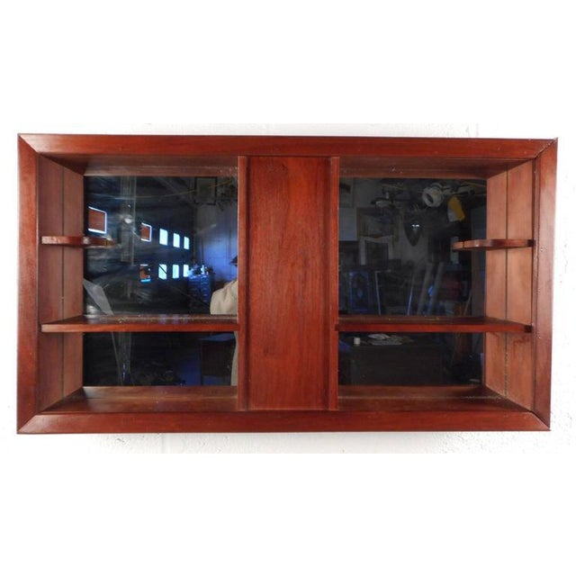 Stunning Mid-Century Modern shadow box features a vintage walnut finish and six shelves to place items for display....