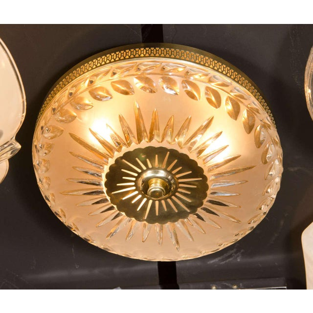 This stunning Hollywood Regency style flush mount chandelier features etched and frosted relief glass with brass fittings....