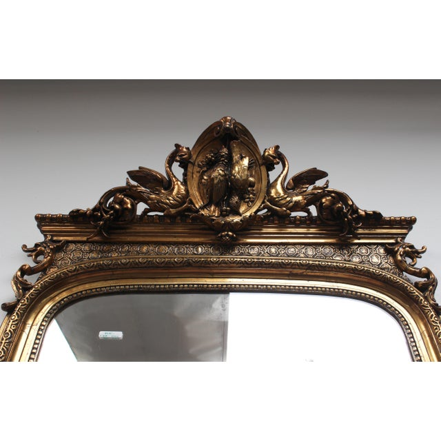 This gilt mirror was bought in and imported from France. It dates to the early 20th century, so there is some normal wear...