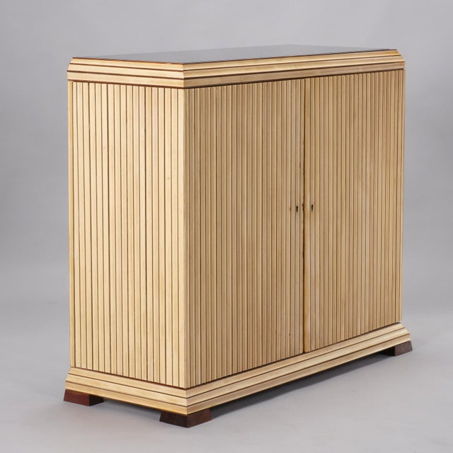 Circa 1940s two door cabinet has light maple reeded exterior with contrasting rosewood feet and an inset black glass top....