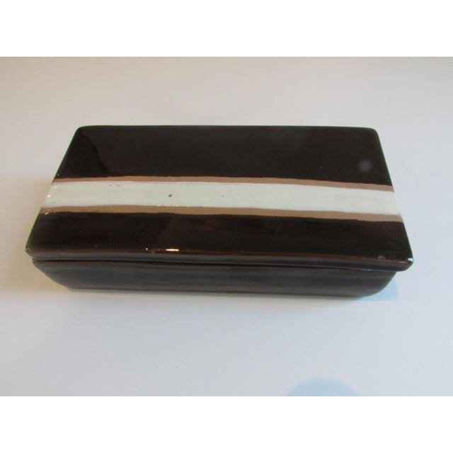 A mid-century modern ceramic box with lid. Gorgeous brownish black glaze with white and caramel stripe. Rosenthal Netter...