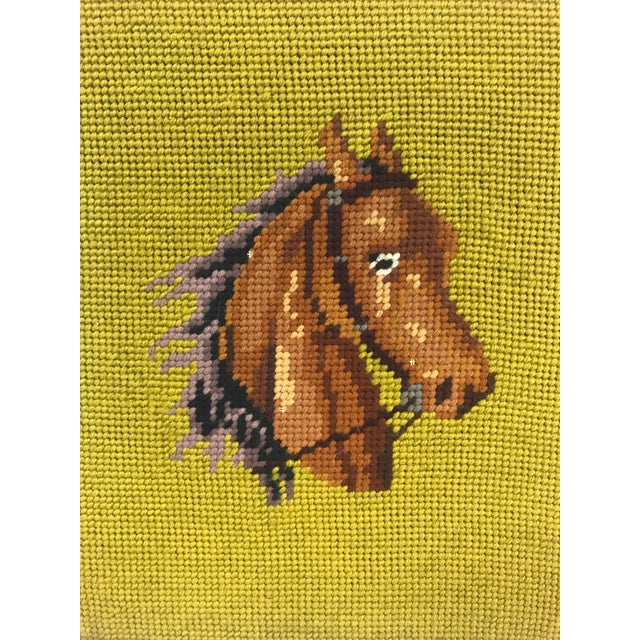 A framed English needlepoint horse against a cool green background. Wood frame. No glass. Wire on back for hanging.
