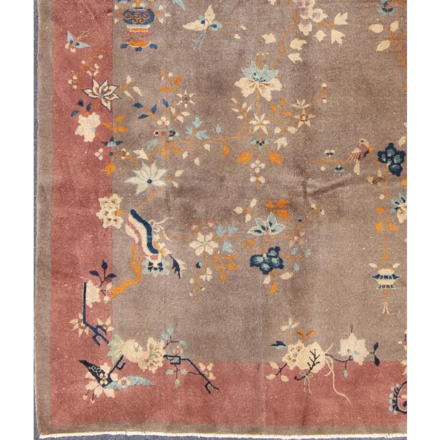 Handwoven in the first part of 20th Century, this antique Chinese rug features a light brown field with a rose and salmon...