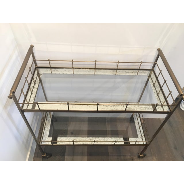2-tiered storage bar cart in vintage brass finish with antique mirror glass shelves and casters for mobility. Has rubber...