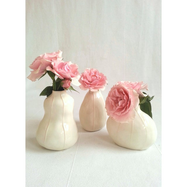 Three white bud vases in unique, handmade original shapes with thin, raised white stripes. This set has 3 shapes. Set...