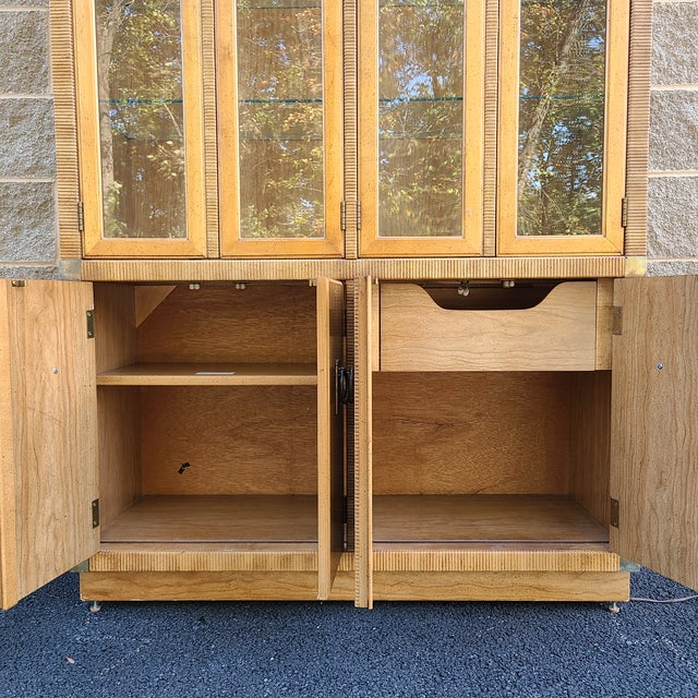 Late 20th century modern Drexel pecan faux bamboo 1 pc lighted breakfront china cabinet. Upper cabinet is lighted and has...