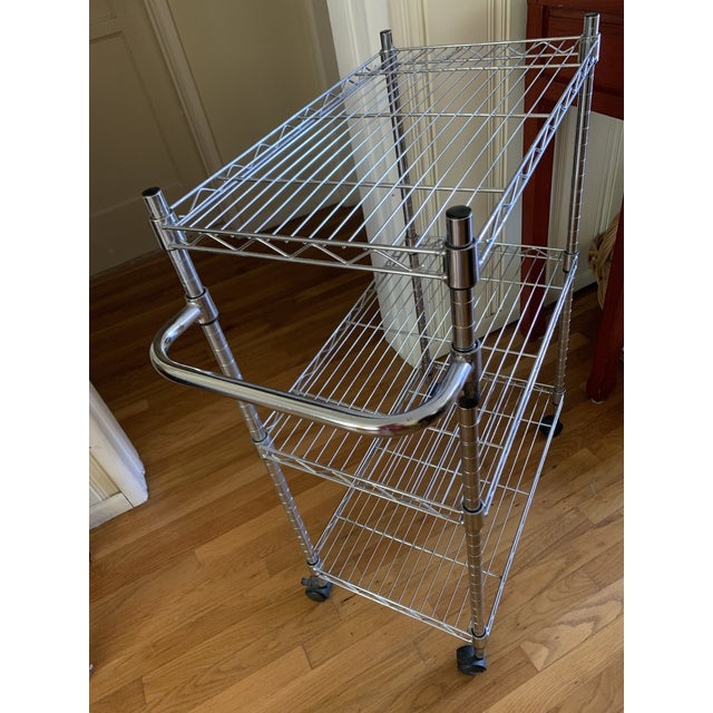 Industrial style stainless steel minimalist bar cart or rolling cart with three shelves and generous storage or display...