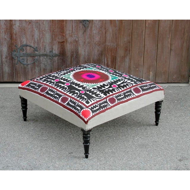 Square ottoman made of foam and cotton on ebonized spindle legs. Upholstered with an antique Suzani textile embellished...