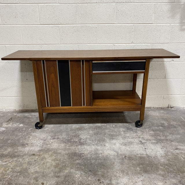 Very cool walnut mid century Bar cart. Two door cabinet and single drawer for storage. The plastic track under the drawer...