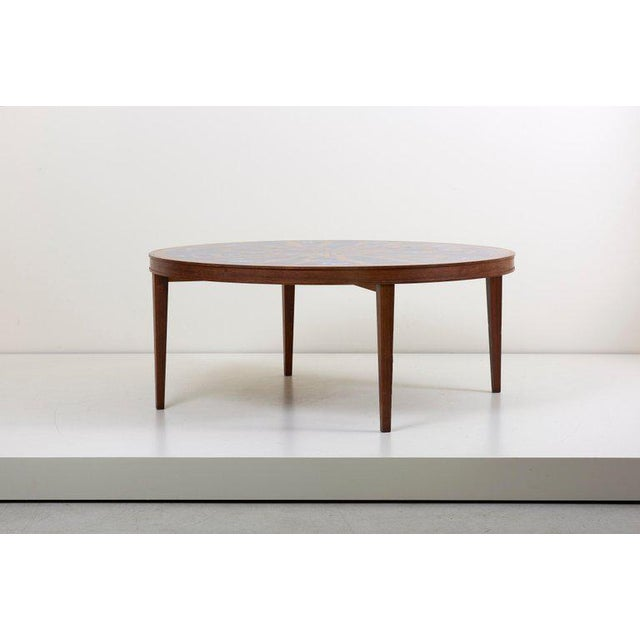 Ultra rare and wooden coffee table with a stunning copper and enamel table top. The coffee table has a impressive size and...