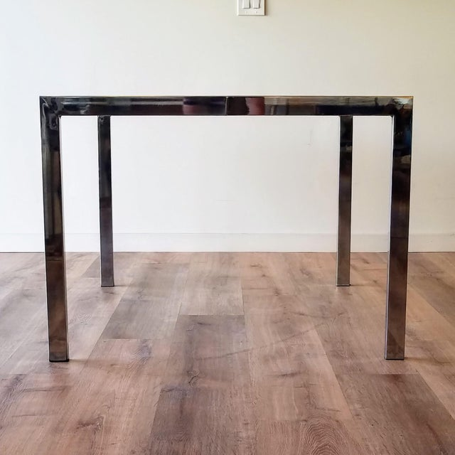 A 1970s chrome and smoked glass square dining table designed by Milo Baughman for DIA-Design Institute America. The...
