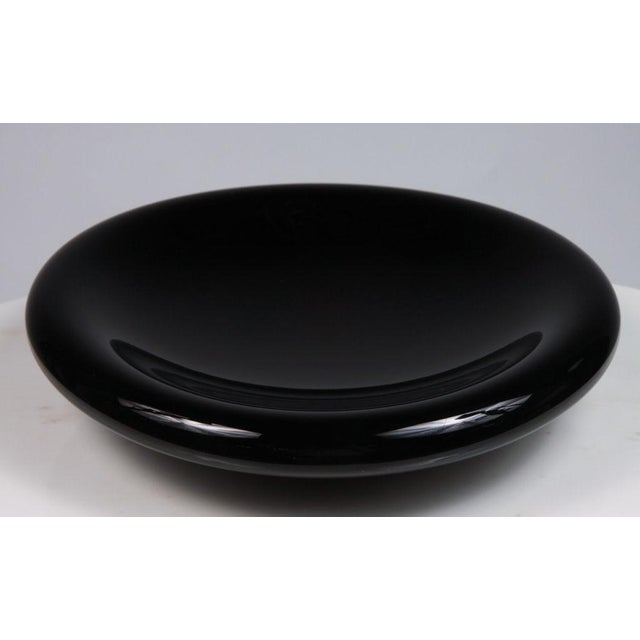 A graceful dish in sable cased glass in a svelte flattened dish form. American, circa 1980.