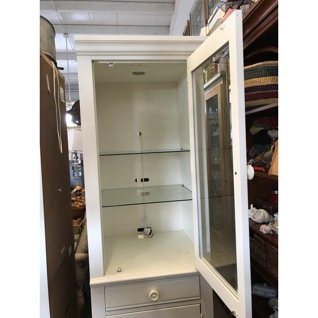 Tall white cabinet by Broyhill Furniture . Open the top glass door and see there are 2 adjustable glass shelves Where you...