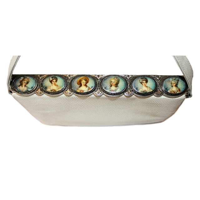 Circa 1960 white lizard purse on an ornately designed silver tone metal frame adorned with six hand-painted portraits...