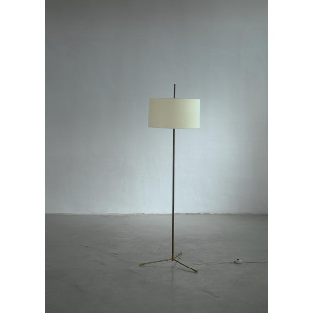 A Mid-Century Danish floor lamp by Svend Aage Holm-Sørensen. The lamp is made of a brass frame with three feet and has a...