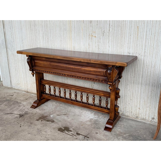 About 18th century Spanish Baroque console table in walnut with three carved drawers and stretcher. Details Dimensions...