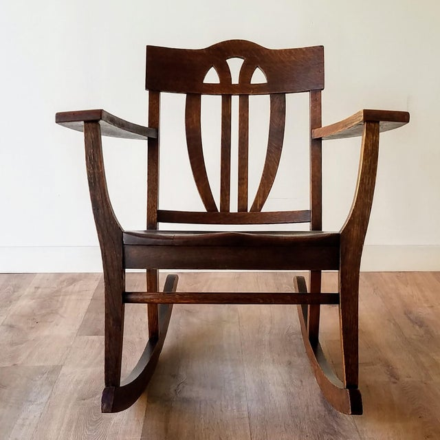 An early 1900s, Arts + Crafts oak rocking chair. This chair features a decorative backrest, wide armrest, and runners that...