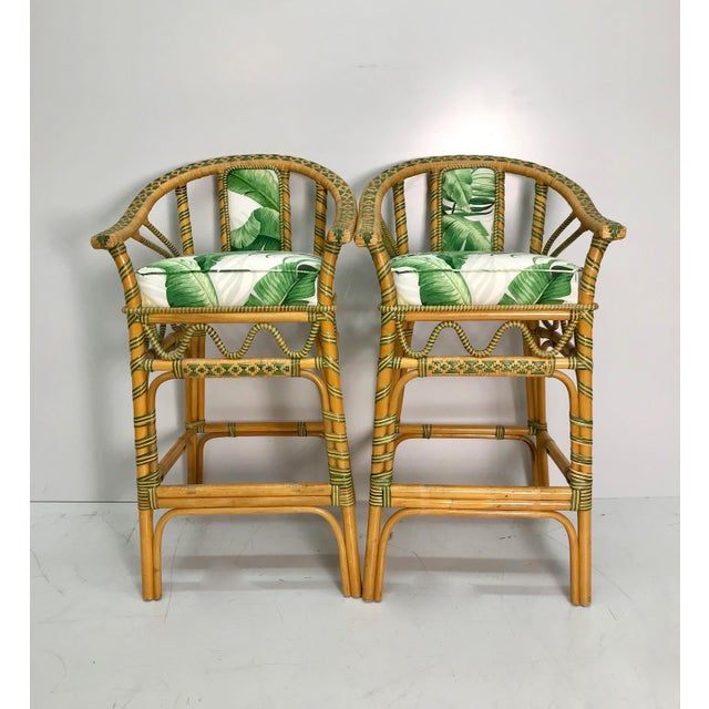 Natural and green woven rattan bar stools. Newly upholstered with a tropical fauna pattern seat and back. Bar height.