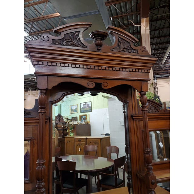 Antique hutch with beveled mirrors on top with small shelf under three drawers, two small doors above an opening flanked...