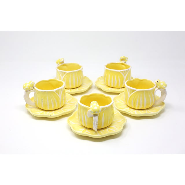 A set of five hand-painted yellow and white flower and frog saucer/cup sets, and two extra saucers. Good vintage...