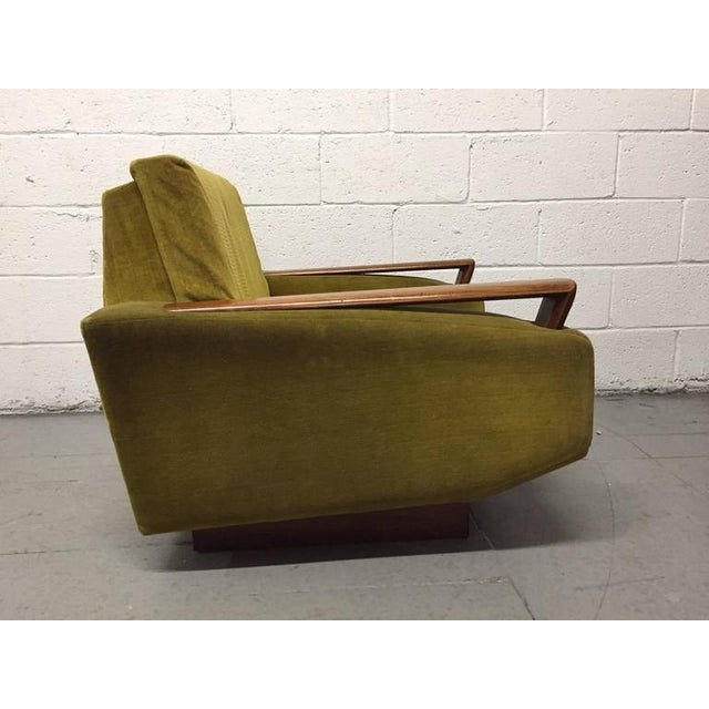 Pair of Jacques Adnet upholstered lounge chairs having up swept walnut arms and loose cushioned seats. Chairs are raised...