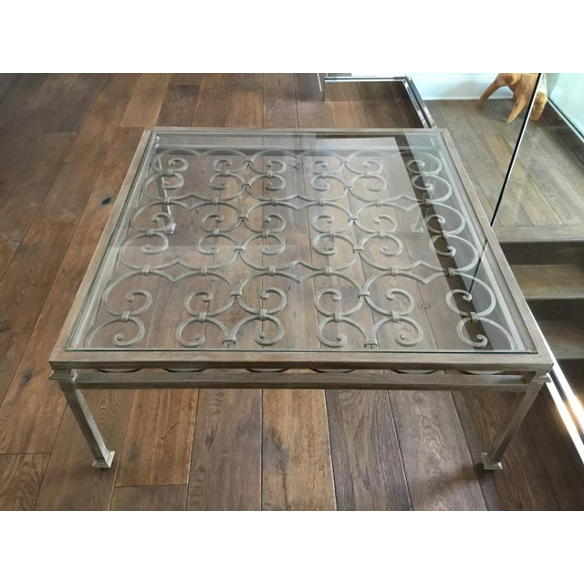 Heavy scrolling-iron coffee table with glass insert. Large surface area with French-inspired details in the iron. The...