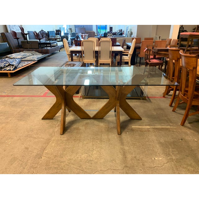 Design Plus presents a West Elm Double Pedestal Wood X Base + Glass Top Table. Walnut stained wood is sculpted into two...