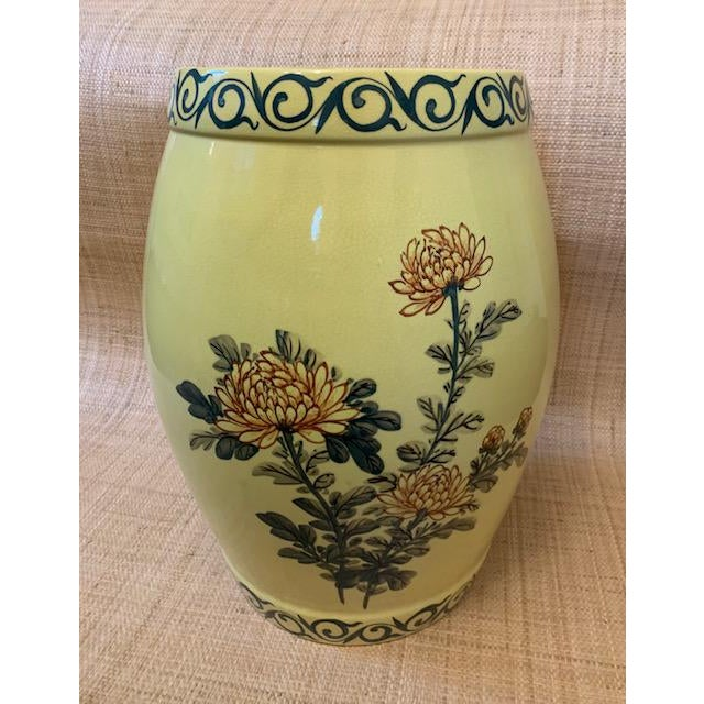 Butter yellow chinoiserie garden stool. Hand painted dahlias on one side, Asian character on the other. Green vines ring...
