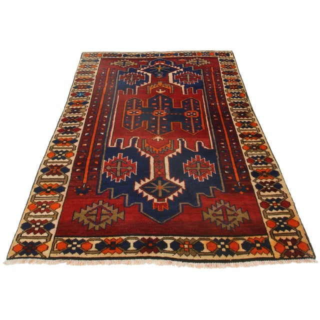 Offered is a Persian Hamedan area rug in tones of red, orange and blue. The hand knotted wool pile features geometric...
