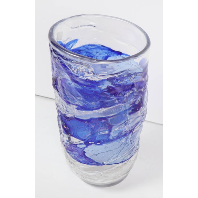A tall vase in clear Murano glass with blue glass applied to the surface. This sculptural piece is perfect for flowers or...