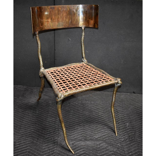 Solid brass sculptural side chair with leather strapping and curve back.(Brass tortoise finish on curve back and dark...