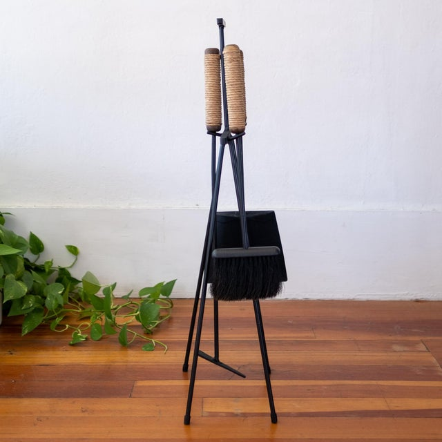 Iron and wood fireplace tools with cord-wrapped handles. Shovel, poker and broom on a floor stand. A striking functional...