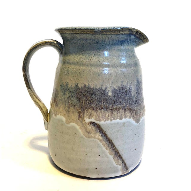 Mid-Century 1970s pale blue stoneware pitcher, signed on the base by the artist. It's the perfect size for water, tea, or...