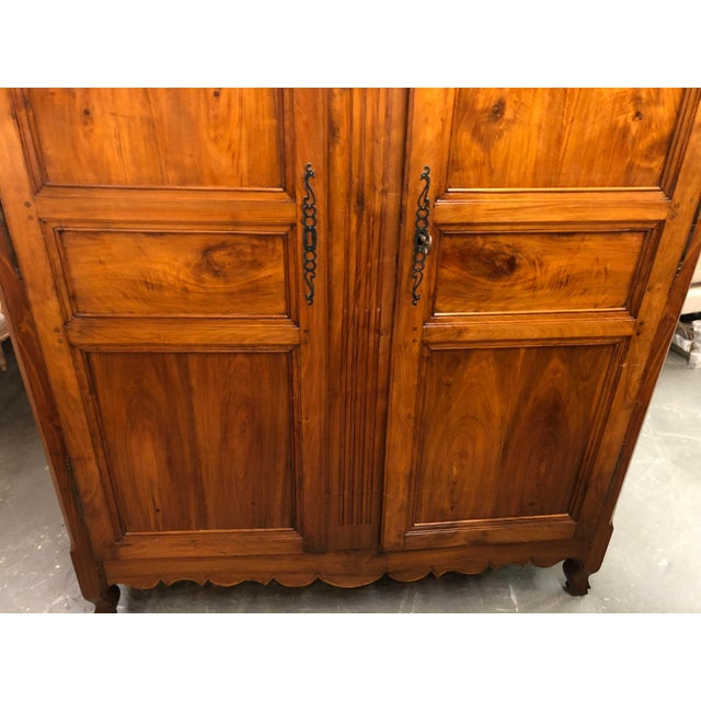 19th century French Louis XV walnut armoire, consisting of molded cornice over a reeded carved frieze and center post....