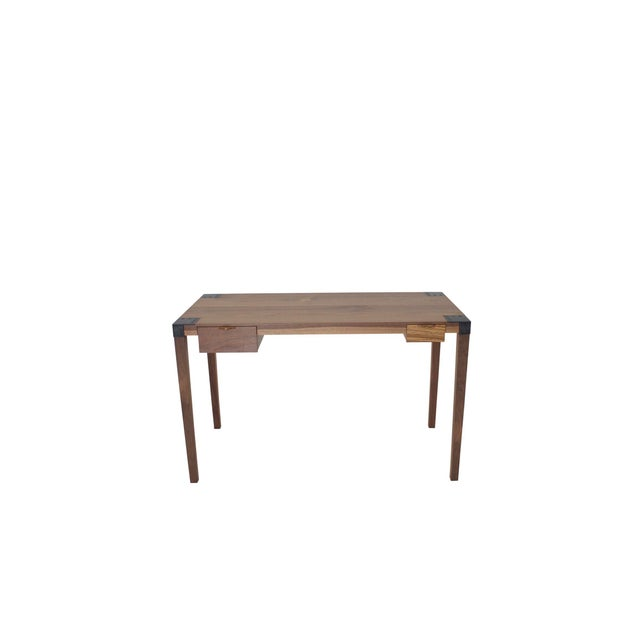 This writer's desk is an exercise in restraint. This sleek desk's tapered legs are made from solid Walnut and are...
