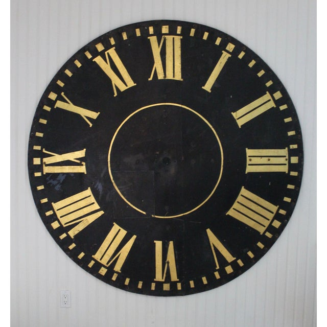 Monumental industrial tower clock face with gilded Roman numbers.