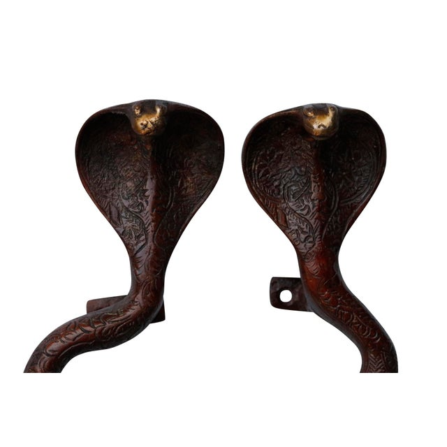 A pair of large red brass cobra door handles or cabinet pulls. Hollywood Regency in style, with intricate carving...