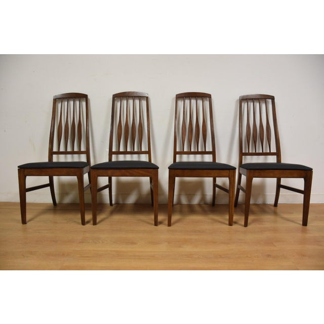 A set of four mid-century modern walnut color dining chairs made by Keller with slatted backs and newly upholstered black...