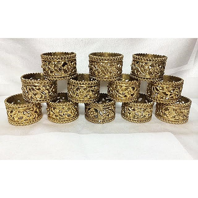 Beautiful set of 12 vintage brass floral filigree napkin rings with beaded borders. The flowers, leaves and vines are very...