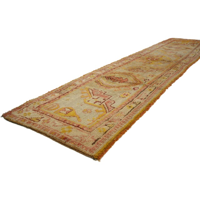 This hand-knotted wool antique Turkish Oushak hallway runner is known as a sampler or wagireh Oushak sampler runner. This...