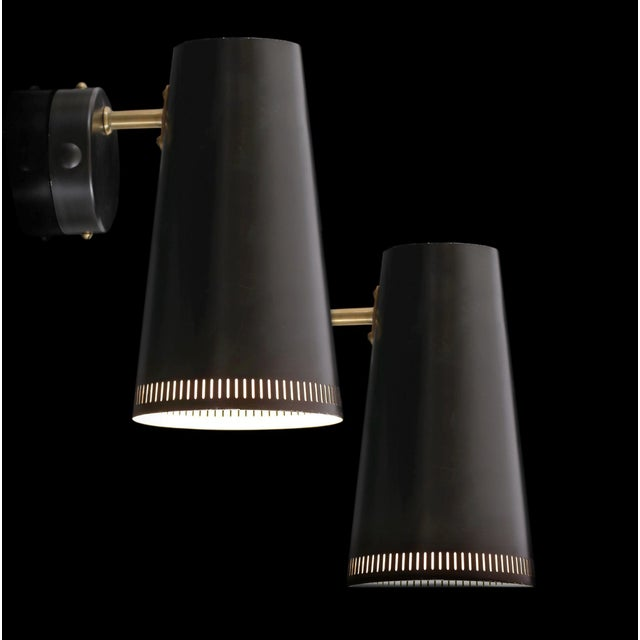 A distinctive pair of wall lights by Paavo Tynell for Taito with black lacquered metal shades and brass stems. Completely...