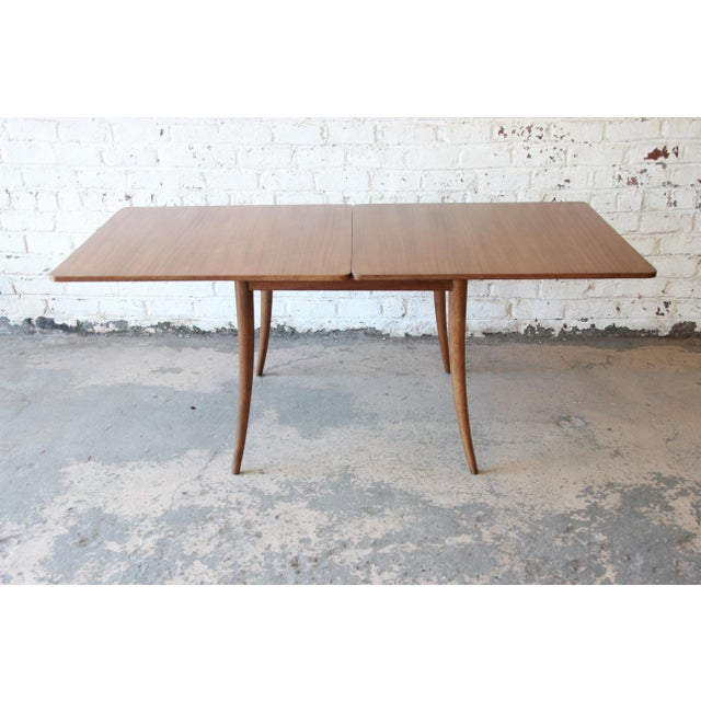Offering an outstanding mid-century modern saber leg flip top extension dining table or game table designed by Harvey...