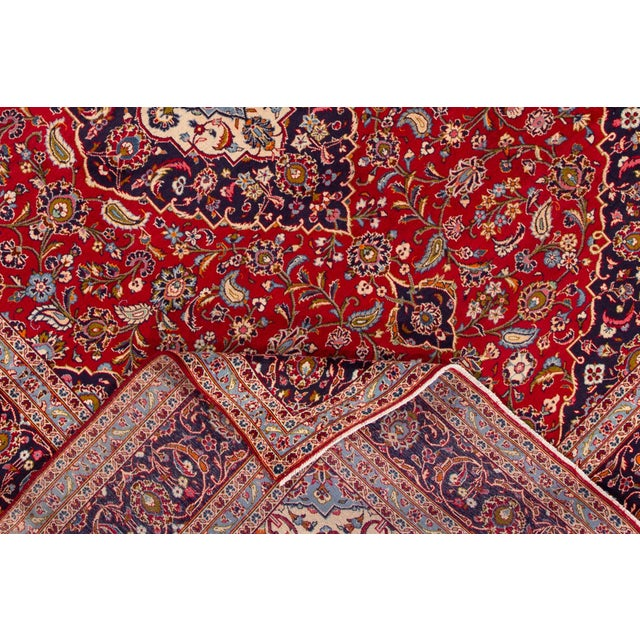 A hand-knotted vintage Persian Kashan rug with a floral medallion design. This piece has great detailing and colors. It...