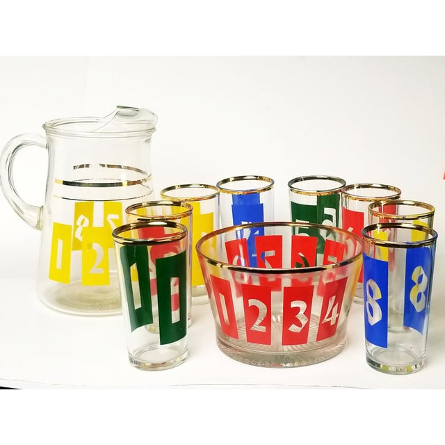 Stunning and fun mid-century decanter, ice bucket and highball glasses numbered in bright primary colors and gold accents...
