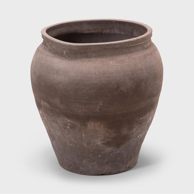 Charged with the humble task of storing dry goods, this capacious earthenware jar is distinguished by its tapered form and...