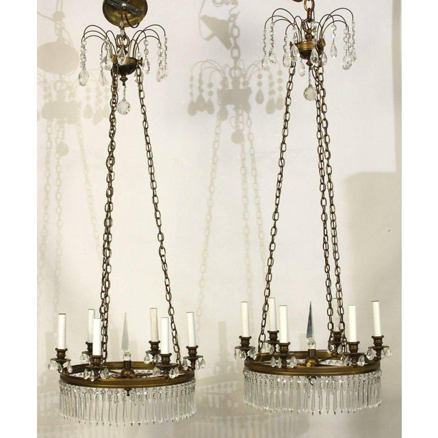 An elegant pair of brass and crystal Regency style six-light chandeliers dating from the 1960s.